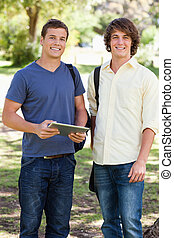 Portrait of two smiling male students with a touch pad