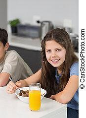 Portrait of two smiling siblings enjoying breakfast