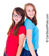 Portrait of two teen girls standing back-to-back