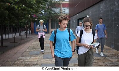 Portrait of teen female and male schoolmates with backpacks and workbooks walking to college campus on warm autumn day