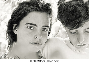 portrait of two teenagers behind some leaves