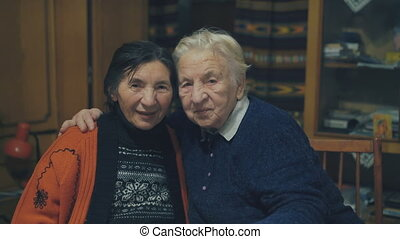 Portrait of two very old women sitting in embraces at the holiday table. 4K
