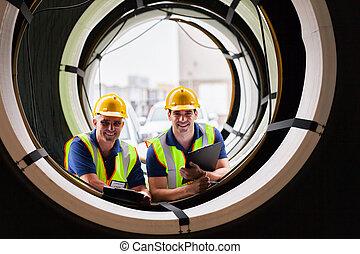warehouse workers standing between industrial tires
