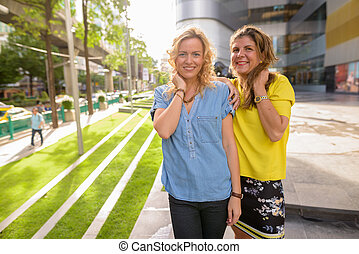 Portrait of two woman smiling together outdoors