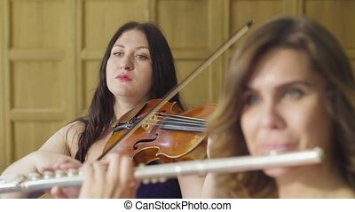 Portrait of two women playing music - Close up portrait of...