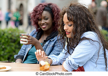 Portrait of two women taking a drink in a bar. Urban background