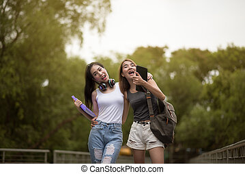 Two young Asia woman friends smiling and walking on street