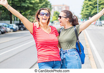 Portrait of two young beautiful lesbian smiling girls in a summer day whit colored t-shirt clothes and jeans
