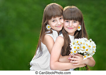 Portrait of two young girlfriends with daisies