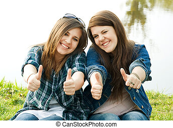 Portrait of two young teenagers laughing and giving the...