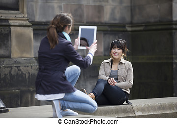 Caucasian and Chinese friends taking photo with Tablet.