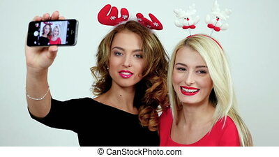Portrait of two young women wearing christmas accessories...