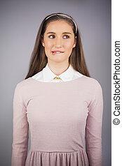 Portrait of uncertain pretty model posing on grey background