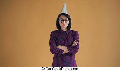 Portrait of unhappy brunette in bright party hat standing...