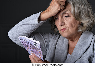 Portrait of unhappy elderly woman with euros