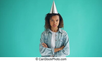 Portrait of unhappy mixed race girl in party hat standing...