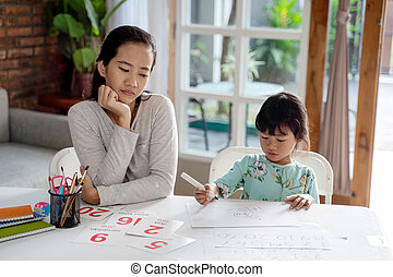 portrait of unhappy mother while teaching her daughter at home