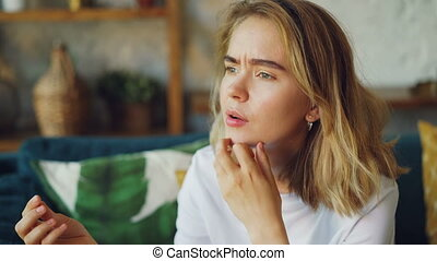 Portrait of unhappy woman looking at engagement ring,...