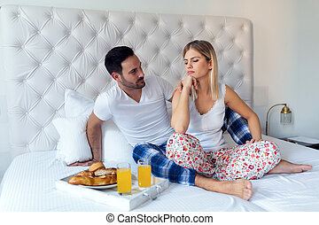 Portrait of unhappy young couple in bedroom