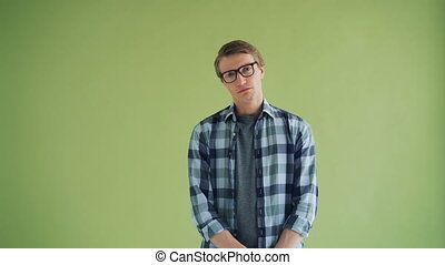 Portrait of unhappy young man looking at camera standing on...