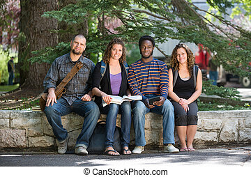 Portrait Of University Students Sitting On Campus