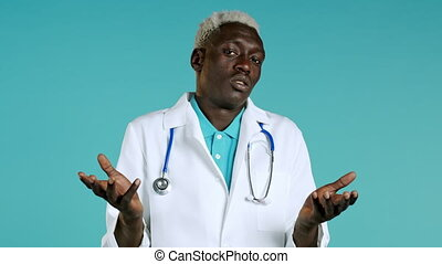 Portrait of unsure african doctor in professional medical white coat shrugs his arms, makes gesture of I don't know, care. Body language. Doc man