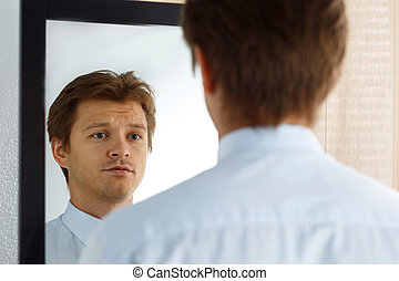 Portrait of unsure young businessman with unhappy face