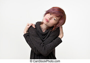 Portrait of unusual informal pretty woman with colorful hairstyle pretending like she is hugging herself. Being proud.