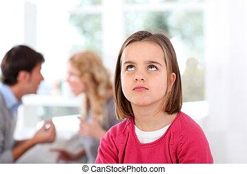 Portrait of upset child with parent's fighting