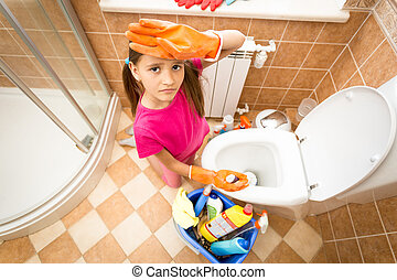 portrait of upset tired girl cleaning toilet with brush -...