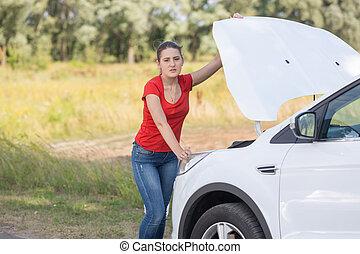 Portrait of upset woman standing at broken car on the roadside