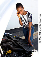 upset young african woman standing by broken down car parked on the side of a road and calling for assistance