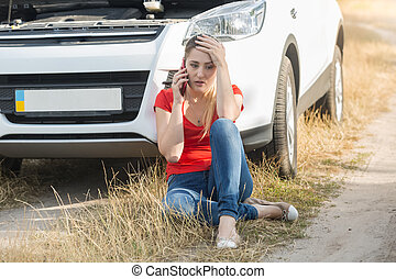 Portrait of upset young woman sitting on ground next to her broken car and talking with service by mobil ephone