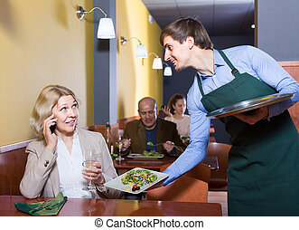 Portrait of waiter and mature woman having dinner