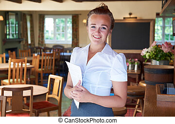 Portrait Of Waitress Holding Menu In Restaurant