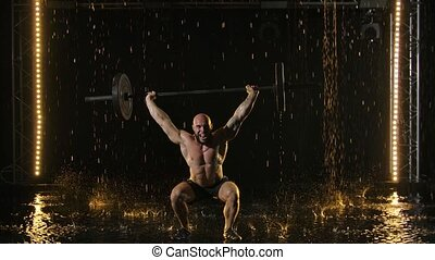 Portrait of Weightlifter performing deadlift exercise with weight bar. Confident young man doing weight lifting workout barbell at crossfit gym. Shot in a dark studio in the rain and staged light. Black background. Slow motion.