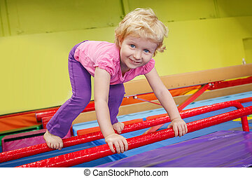 happy smiling baby girl child doing exercises in gym