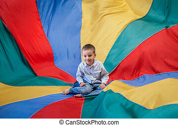 child boy toddler sitting in the center of playground rainbow parachute