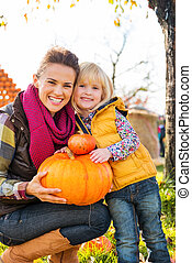 Portrait of woman and child holding pumpkins in autumn outdoors