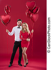 Portrait of woman and man with red balloons