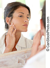 Portrait of woman applying foundation makeup on her face