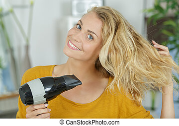 portrait of woman blowdrying her hair