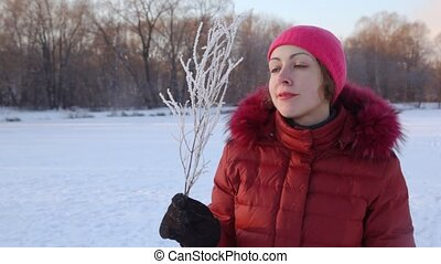 portrait of woman blows to branchlet covered with hoarfrost...