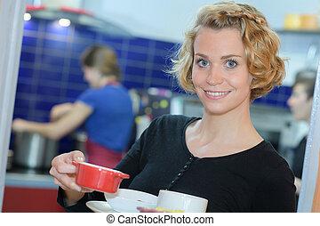 Portrait of woman carrying ramekin dish