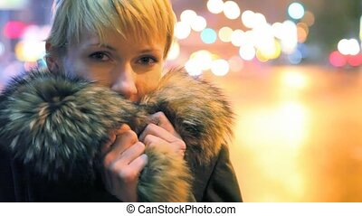 portrait of woman, city lights in background