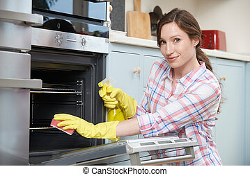 Portrait Of Woman Cleaning Oven At Home