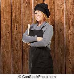 portrait of woman cook wearing apron against a wooden wall