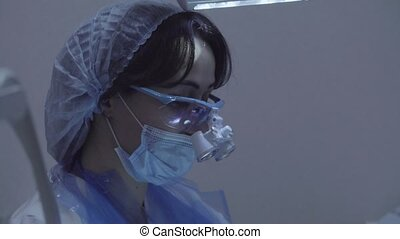woman dentist with oculars on head at work - Portrait of...