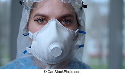 Portrait of woman doctor weaing protective suit during coronavirus pandemic, . Hazard suit, respiratory mask, gloves and glasses clinic or hospital. Protection from coronavirus, covid-19 epidemic concept