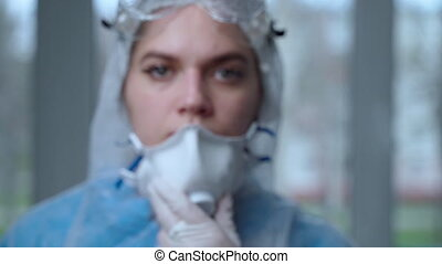 Portrait of woman doctor weaing protective suit during ...
